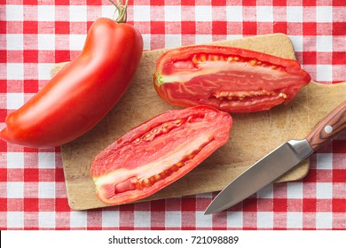 Halved San marzano tomatoes on cutting board. Top view