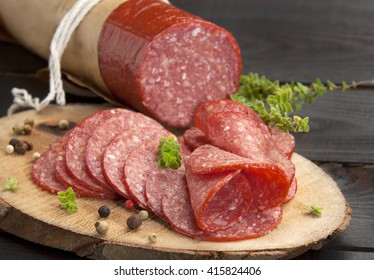 halved in slices delicious salami served on a slice of wood with thyme and ground pepper