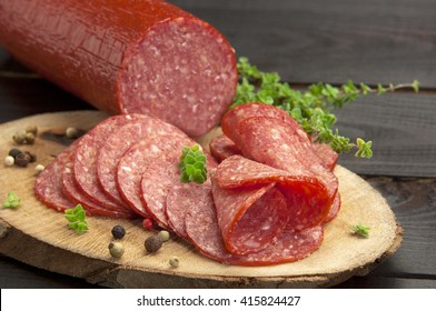 halved in slices salami served on a slice of wood with thyme and ground pepper