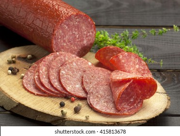 halved in slices turkey salami served on a slice of wood with thyme and ground pepper