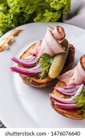 Halves baked potato with pickled cucumber, dill, salo and onion on wooden table