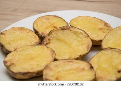 Halves of baked potatoes on a white plate.