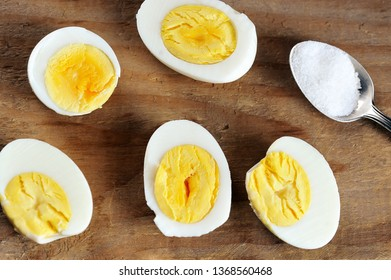 halves of boiled egg and salt in a teaspoon on a wooden rustic background