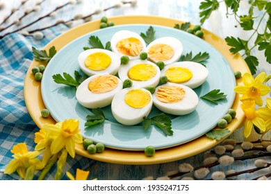 Halves of boiled eggs on a blue plate, close up view. Easter, a healthy snack