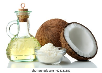 halves with coconut oil and coconut flakes in glass bowl on white isolated background