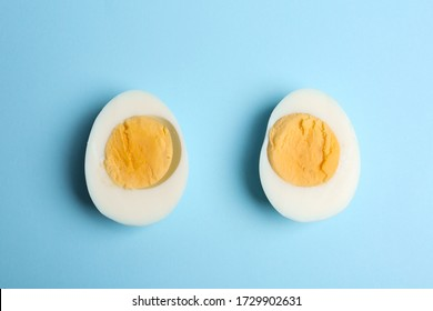 Halves of fresh hard boiled chicken egg on light blue background, flat lay