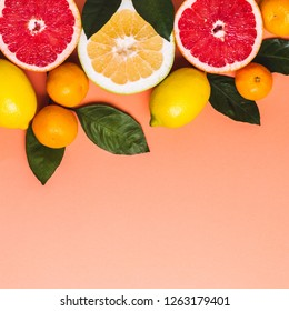 Halves of grapefruit, lemons and tangerines. Living coral background. Color trend 2019.
