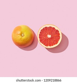 Halves juicy grapefruit presented on a pink background with reflection of shadow and copy space. Dietetic food. Top view