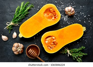 Halves of raw organic butternut squash with spices and ingredients for making on a black slate, stone or concrete background.Top view.