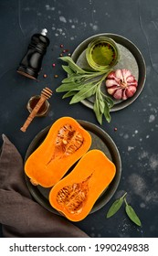 Halves of raw organic pumpkin or butternut squash with sage leaf, multicolored pepper garlic, honey, salt and pepper on black slate, stone or concrete background. Food background. Top view.