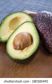 Halves of ripe avocado on wooden surface. Closeup.