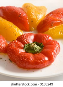 Halves of yellow and red sweet peppers on white plate with olive oil based dressing