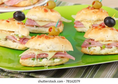 Ham and cheese appetizers on a biscuit topped with olives