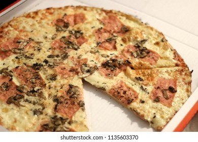 Ham, cheese and mushroom pizza in a box. One piece is cut out. Selective focus.
