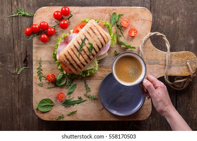 Ham and cheese panini sandwich with salad and cherry tomatoes with fimale hand holding a cup of coffee served on rustic wooden board over an old wooden background. Top view