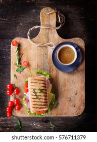 Ham and cheese panini sandwich with salad and cherry tomatoes served on rustic wooden board over an old wooden background with the space on top