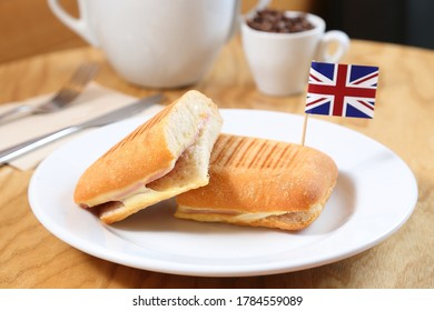 Ham and Cheese Panini Small Bread Roll with British flag on top Wooden background