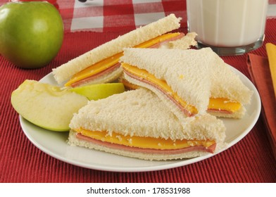A ham and cheese sandwich with an apple and milk