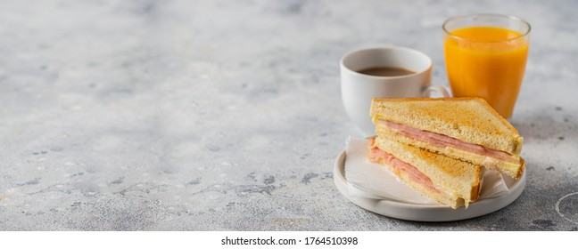 Ham and cheese sandwich, coffee with milk and orange juice on table in coffee shop. Typical breakfast in many countries. Large image for banner.