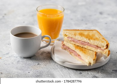 Ham and cheese sandwich, cup of coffee with milk and orange juice glass on concrete table in coffee shop at the morning. Typical breakfast in many countries.