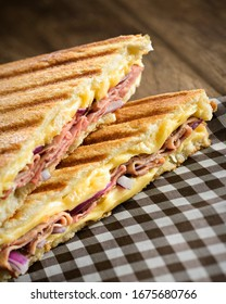 Ham and cheese sandwich on a checkered napkin, with melted cheese, ham and onion, on a toasted sliced bread.