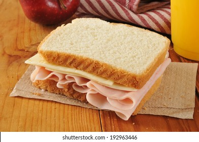 a ham and cheese sandwich with orange juice and an apple
