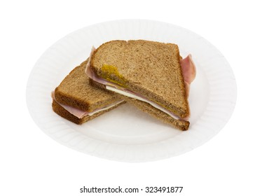 A ham and cheese sandwich that has been cut in half on a white paper plate atop a white background.