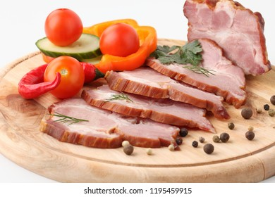 Ham chopped in thin slices and decorated with spices and vegetables on a white background