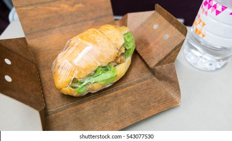 Ham croissant wrapped in box , croissant and water on table , Food was served in the plane