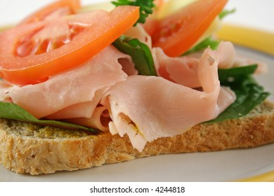 Ham, lettuce, tomato and cheese open sandwich on wholemeal bread.