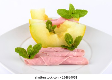 Ham and melon on white background.