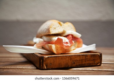 Ham and mozzarella sandwich on a wood chopping board. Selective focus.