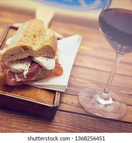Ham and mozzarella sandwich on a wood chopping board. Selective focus and vintage effect