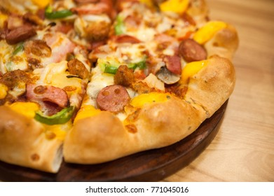 ham and pepper pizza lay on wooden plate,delicious pizza put on wooden plate,selective focus
