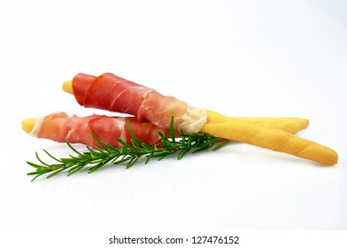 Ham (prosciutto) and grissini on white background