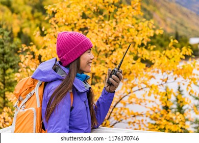 Ham radio gear outdoor hiking girl talking on radio in fall nature with camping equipment. Amateur radio hobby hiker.