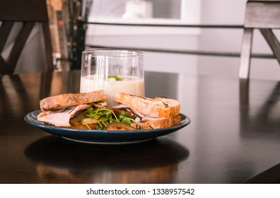 ham sandwich and broccoli soup on dining table home interior