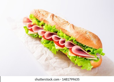 Ham sandwich with cheese and salad on a paper bag on white