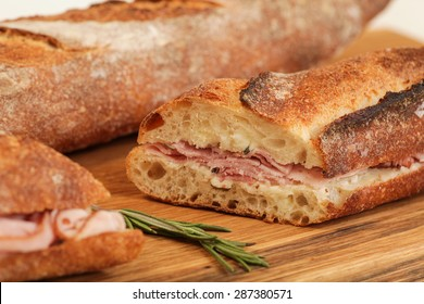 Ham sandwich with herb butter on a wood cutting board.
