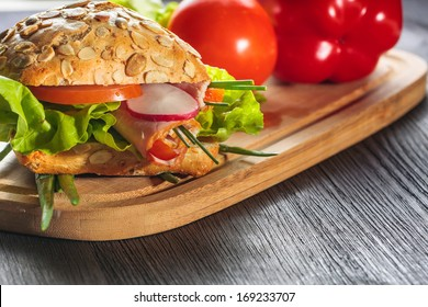 ham sandwich with lettuce on wood background