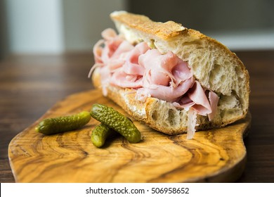 Ham sandwich on a French baguette roll served with green pickles on a wooden cutting board