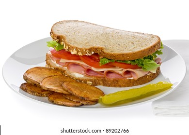 Ham sandwich with swiss cheese, lettuce and tomato with homemade potato chips on a white plate.