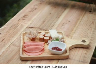 Ham and sausage in wooden dish Breakfast