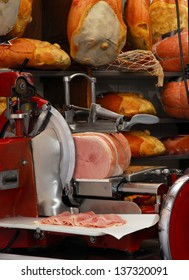 Ham slicer and prosciutto ham in a warehouse.