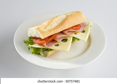 Ham and Swiss cheese baguette on white plate