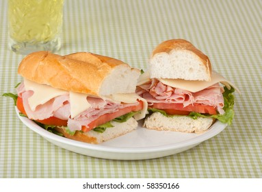 Ham and swiss cheese sub sandwich with lettuce and tomato and a drink