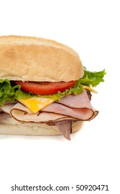 A ham and tureky sandwich on a hoagie bun with lettuce, tomato and cheese on a white background