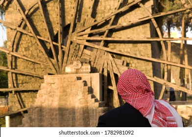 Hama, Syria. November 6th 2009An old Syrian man sits beside one of the famous ancient waterwheels of Hama, Syria.