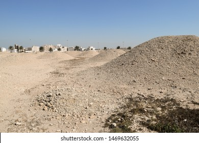Hamad, Bahrain - February 13 2019: Sumerian Dilmun Burial Mounds against the backdrop of modern buildings of Hamad town in Bahrain