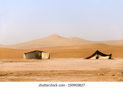 Hamada du Draa (Morocco stone desert)  sand dunes with tents in foreground